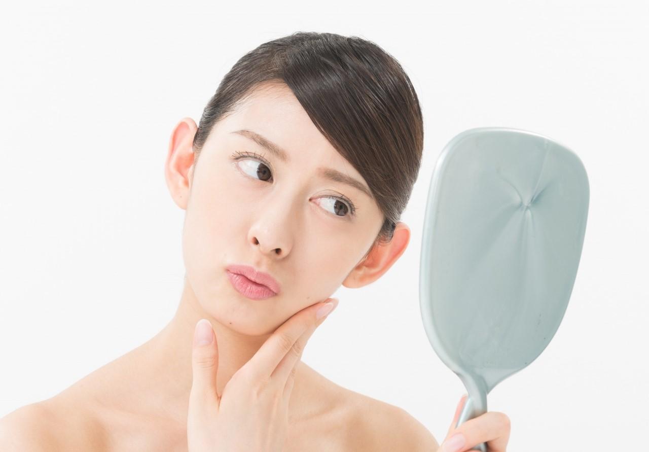 鏡で顔をみる女性